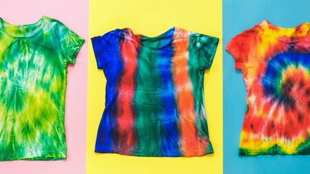 Red, yellow and blue background with tie dye t-shirts. White clothes painted by hand. Flat lay.
