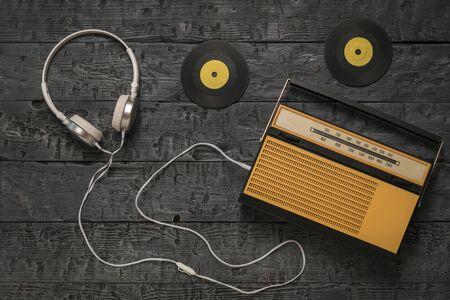 Retro radio with headphones and yellow vinyl discs on a wooden background. Radio engineering of the past time. The view from the top.