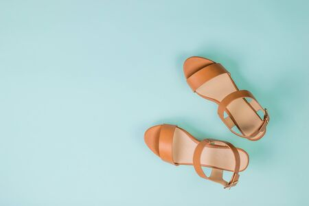 Women's leather stylish sandals on a light blue background. Summer shoes for women. Flat lay. The view from the top.