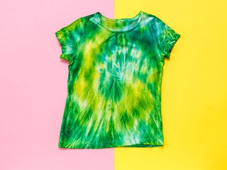 Red and yellow background with tie dye t-shirt. White clothes painted by hand. Flat lay. Place for text. Banque d'images