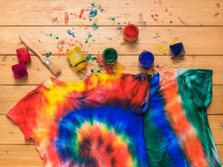 The process of painting a t-shirt in the style of tie dye in the form of a spiral. White clothes painted by hand. Flat lay. Foto de archivo