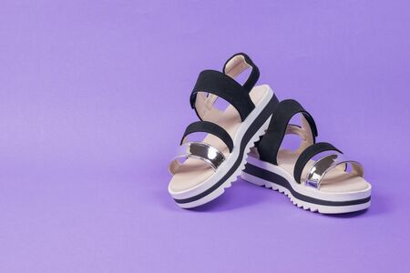 White and black women's sandals on a purple background. Summer shoes for women.