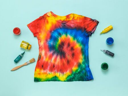 Hand-painted t-shirt in tie dye style and paint on a light blue background. White clothes painted by hand. Flat lay. Place for text.