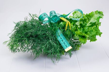 Basket with salad and dill and measuring tape on a white table. The concept of a diet for weight loss.