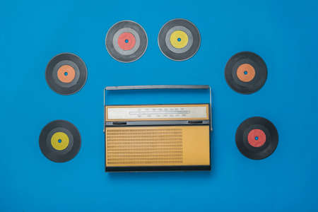 Retro radio and multicolored vinyl discs on a blue background. Radio engineering of the past time. The view from the top.