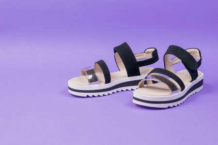 Stylish summer black women's sandals on a lilac background. Summer shoes for women.