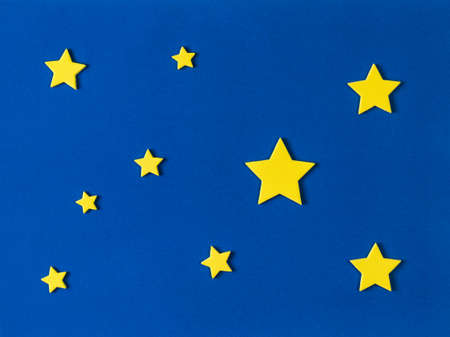 Application of blue paper background and yellow stars. Creativity from paper and cardboard.