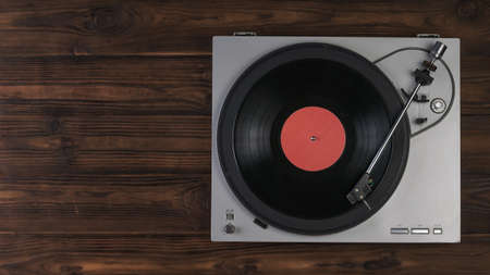 Vinyl record player on a brown wooden background. The view from the top. Music on vinyl discs.