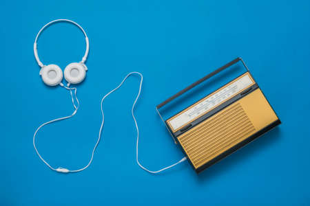 White headphones with a wire and a retro radio on a blue background. Radio broadcast live. Vintage technique. 版權商用圖片