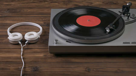 A vinyl record player and headphones on a dark wooden table. Music on vinyl discs.