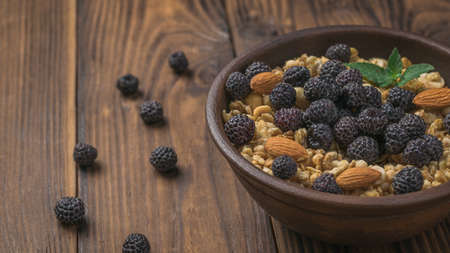 Scattered black raspberries and a bowl of granola on a wooden background. The dish is rich in fiber.