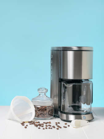 Coffee maker and coffee beans in a glass jar on a white table. The concept of a classic Breakfast.