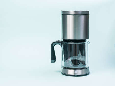 Silver drip coffee maker on a light blue background. The concept of a classic Breakfast.