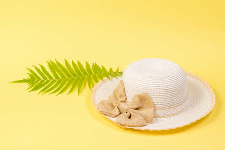 A large white hat and a palm leaf on a yellow background. Concept of recreation on the sea coast.