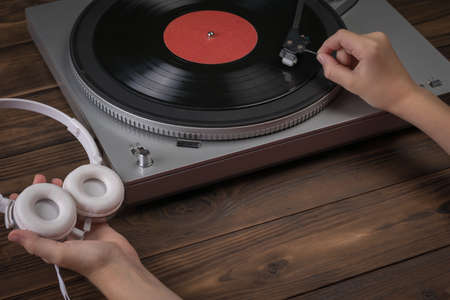 Hands holding white headphones and placing a vinyl disc on the player. Music on vinyl discs.