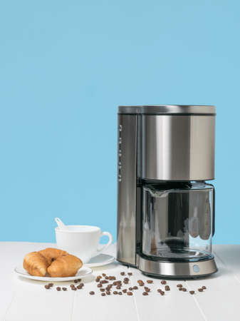 A plate of croissants, a coffee maker, and scattered coffee beans on a white table. The concept of a classic Breakfast.