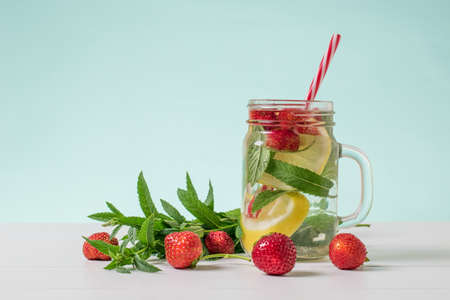 Strawberry berries and mint leaves next to a mug of cold water. Freshly prepared refreshing cold vitamin drink. Reklamní fotografie