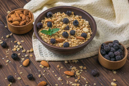 Granola with black raspberries and almonds on a wooden table. The dish is rich in fiber.