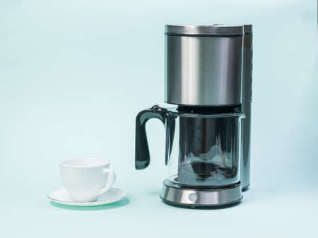 White coffee Cup and drip coffee maker on a blue background. The concept of a classic Breakfast.