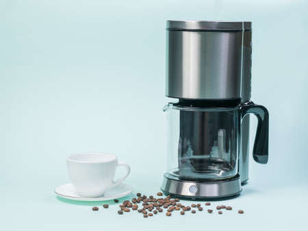 White coffee Cup, coffee maker and scattered coffee beans on a blue background. The concept of a classic Breakfast.