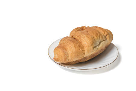 Fresh croissant on a white plate isolated on a white background. Breakfast dish.