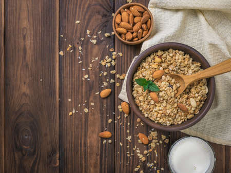 Milk, almonds and granola in a clay bowl on a wooden table. The view from the top.