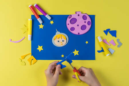 A child makes a picture out of paper on the theme of space. The creativity of paper. Stock Photo