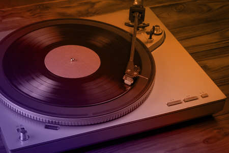 A tinted vinyl record player on a wooden table. Music on vinyl discs.