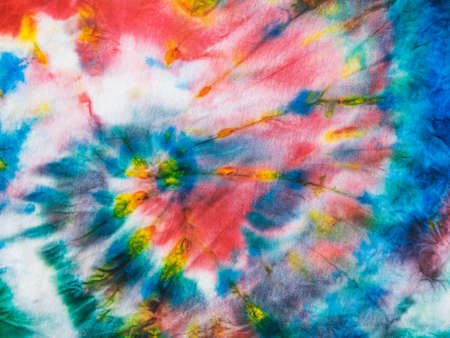 Hand-drawn tie dye pattern on white fabric. White clothes painted by hand. Flat lay.