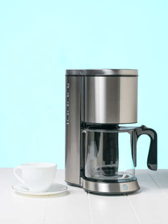 Coffee maker and white coffee Cup on a white table. The concept of a classic Breakfast.