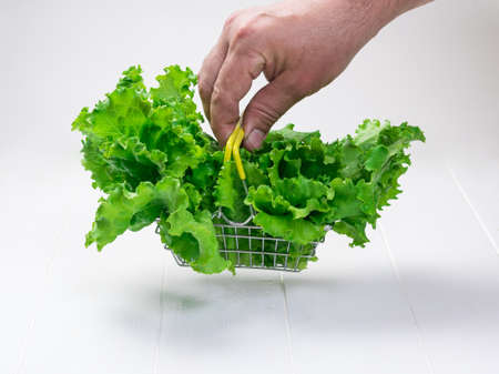 A man's hand holds a metal salad basket over a white table. Concept of dietary healthy nutrition.