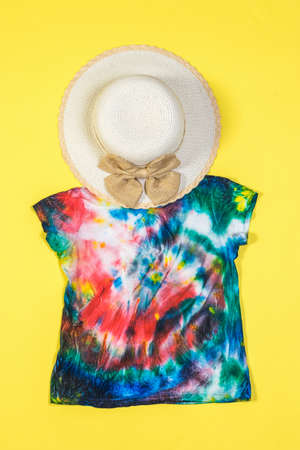 A large hat and tie dye t-shirt on a yellow background. White clothes painted by hand. Flat lay.