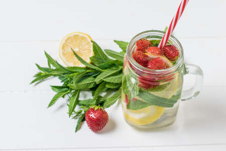 A mug of cold water with berries and lemon on a white table. Freshly prepared refreshing drink with berries, lemon and mint.