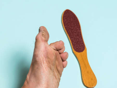 A man's big toe with damaged skin and a hand-held grooming device. Treatment of leg skin.