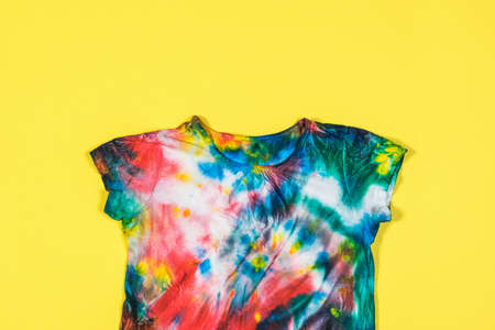 T-shirt with short sleeves in tie dye style on a yellow background. White clothes painted by hand. Flat lay.