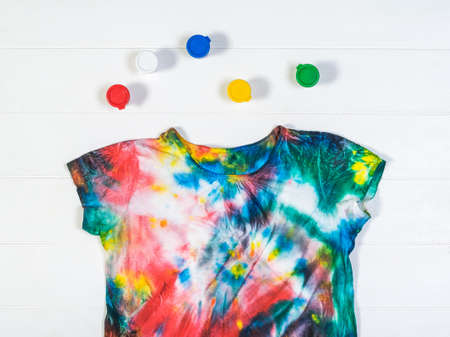 Round paint cans and a tie dye t-shirt on a white table. White clothes painted by hand. Flat lay. Stock Photo