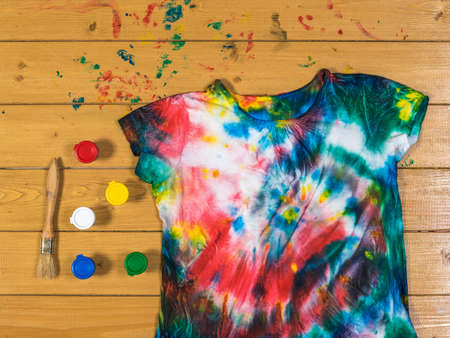 Paint cans with a brush and a tie dye t-shirt on a wooden table. White clothes painted by hand. Flat lay.