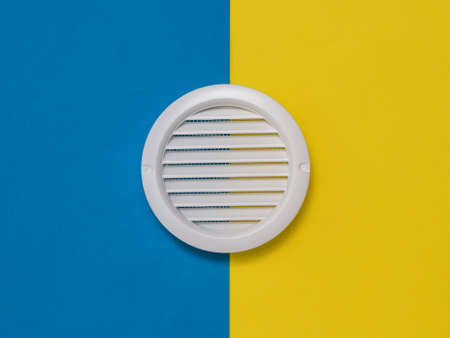 White ventilation grate on a yellow and blue background. Devices for fresh air supply. Reklamní fotografie