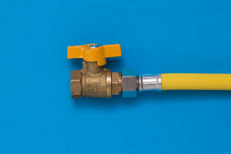 Gas tap with yellow hose on a blue background. Organization of natural gas supply. Stock Photo