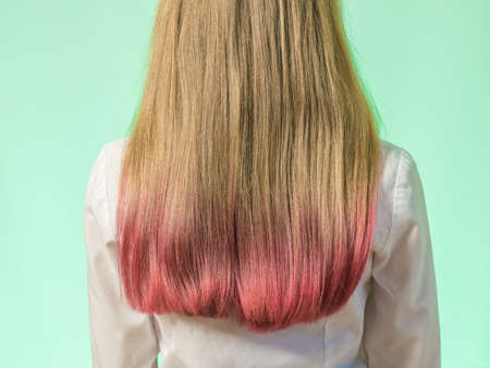A girl with dyed hair tips on a green background. Space for your text.