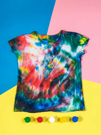 T-shirt in tie dye style and paint on a three-color background. White clothes painted by hand. Flat lay. Stock Photo