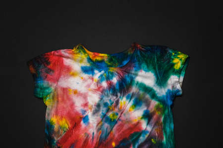 Multi-colored tie dye t-shirt on a black background. White clothes painted by hand. Flat lay. Place for text.