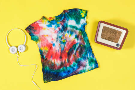 Tie dye t-shirt, headphones and radio on a yellow background. White clothes painted by hand. Flat lay.