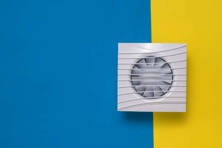 Square fan on a yellow and blue background. Equipment for the removal of dirty air.