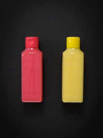 Pink and yellow plastic bottles on a black background. Plastic utensils for the storage of liquids.