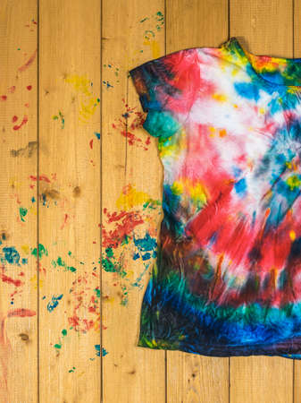 Tie dye-style t-shirt on wooden boards. White clothes painted by hand. Flat lay.