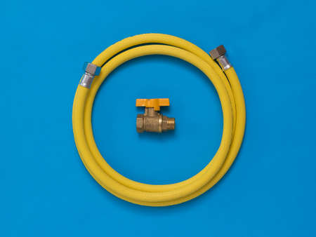 Yellow hose and gas tap on a bright blue background. Organization of natural gas supply.