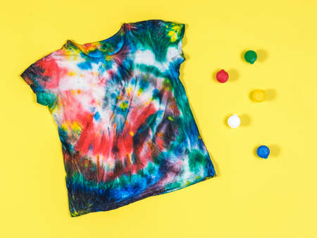 Tie dye t-shirt and colorful paint cans on a yellow background. White clothes painted by hand. Flat lay. Stock Photo