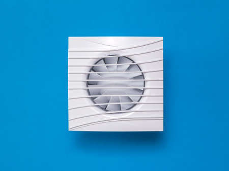 White exhaust fan on a bright blue background. Equipment for the removal of dirty air. Stock Photo