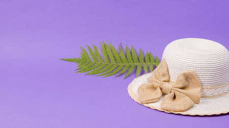 A large palm leaf and a large hat on a lilac background. Concept of recreation on the sea coast. Stock Photo